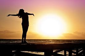 woman sun arms open